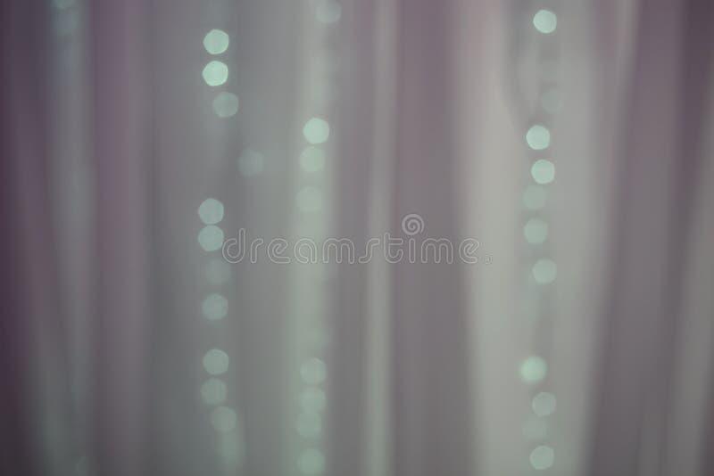 Pastellfärgad blå glödande bakgrund Defocused bakgrund med den blinkaljus och gardinen royaltyfri bild
