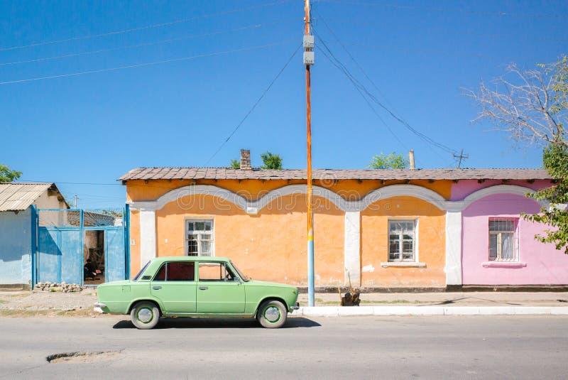 Pastellfärgad färg av hus och en gammal bil royaltyfria bilder