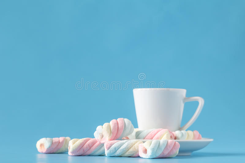 Pastellfärgad marshmallow och en vit kopp på en blå bakgrund Söt u arkivbilder