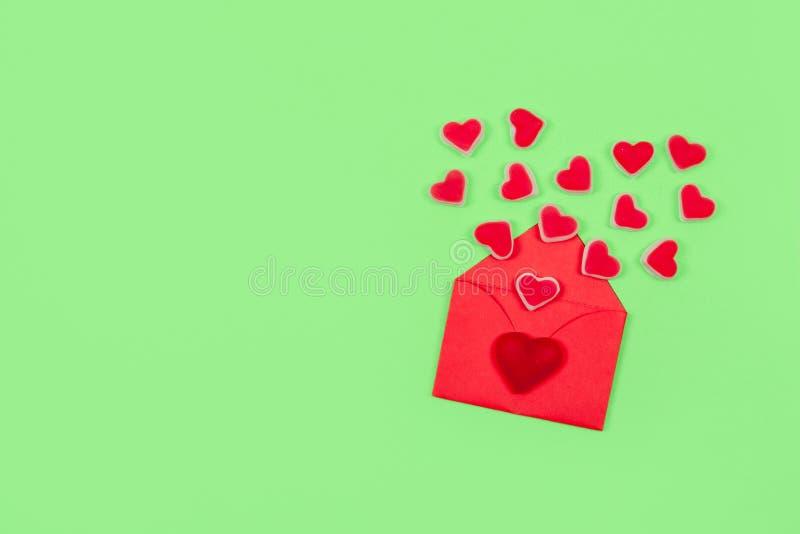 Pastellfärgad minsta idérik bakgrund för valentindag Textförälskelse är, det röda kuvertet många hjärtaformgodisar på grön bakgru royaltyfri bild