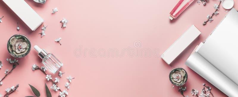 Pastellfärgad rosa skrivbords- bakgrund för skönhet med öppen tidskriftåtlöje upp, moderna skönhetsmedel och blomningfilialer, bä royaltyfri bild