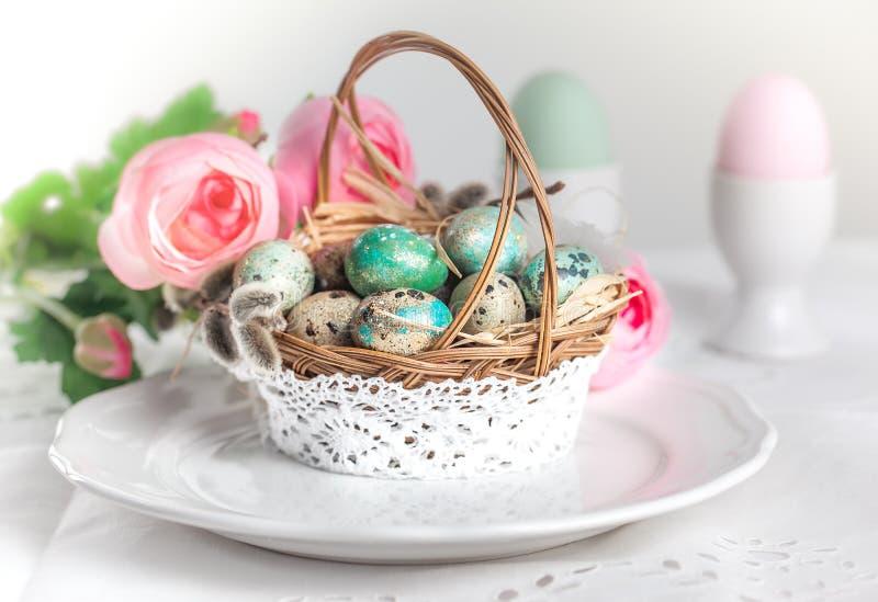 Pastellfärgade easter ägg och blommor i korg royaltyfri foto