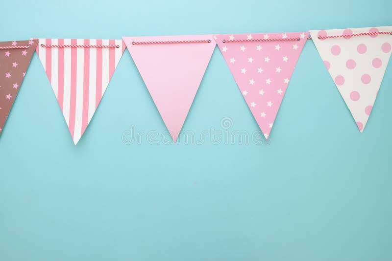 Pastellfärgbunting- eller partiflaggor på blå bakgrund Parti- eller årsdagbakgrund royaltyfri fotografi