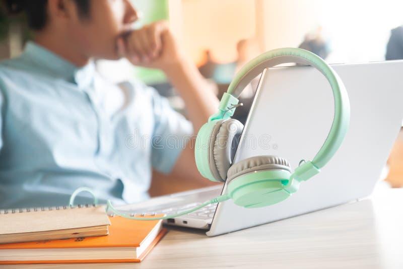 Pastellfärghörlurar, bärbar datordator och anteckningsböcker på workspaceskrivbordet med den stiliga mannen på bakgrund Funktions arkivfoton