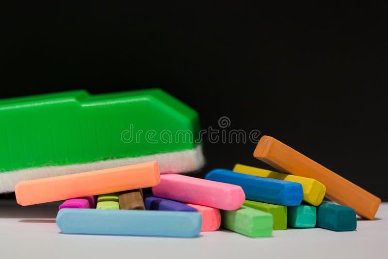 Pastelli del gesso e gomma di lavagna verde fotografie stock libere da diritti