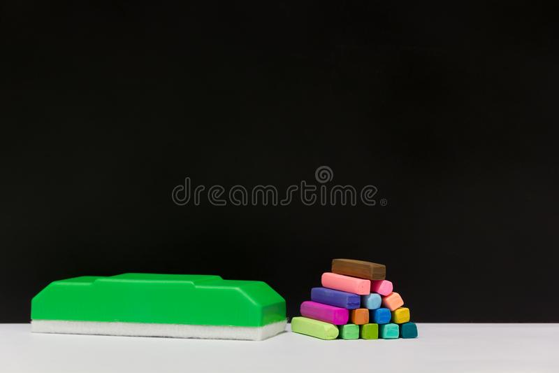 Pastelli del gesso e gomma di lavagna verde fotografie stock