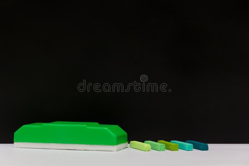 Pastelli del gesso e gomma di lavagna verde fotografia stock