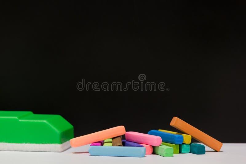 Pastelli del gesso e gomma di lavagna verde immagine stock