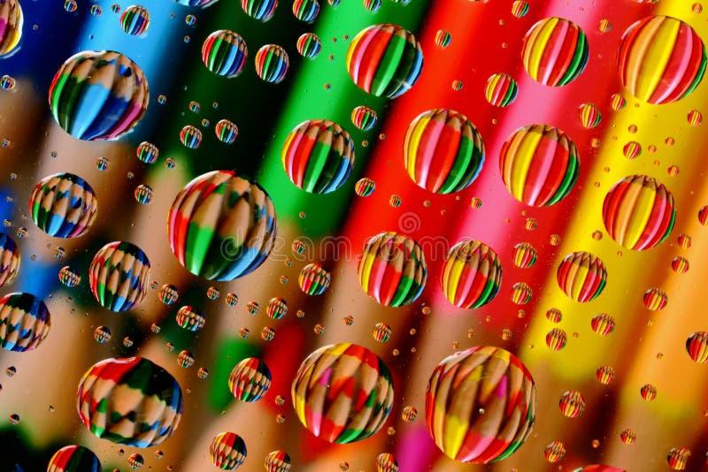 Pastelli della matita attraverso le goccioline di acqua fotografia stock