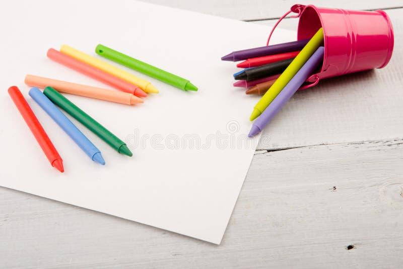 pastelli variopinti e carta in bianco sullo scrittorio fotografia stock