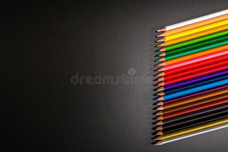 Pastelli variopinti su un fondo nero immagini stock