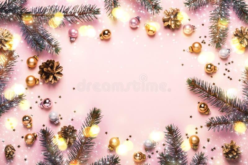Pastellrosa-Weihnachtshintergrund Festlicher Rahmen von Tannenzweigen, von Spielwaren und von goldenen bokeh Lichtern stockfoto