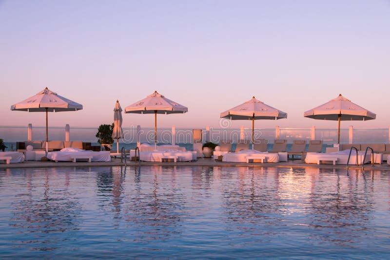 Pastellsonnenuntergang-Licht über Swimmingpool und Sun-Betten stockbild
