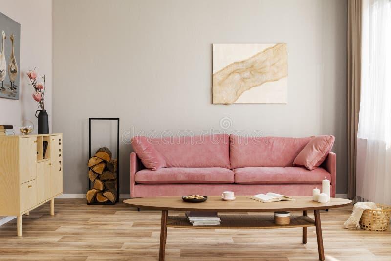Pastelowy abstrakcjonistyczny obraz na beż ścianie za aksamit menchii kozetką w prostym żywym pokoju zdjęcia stock