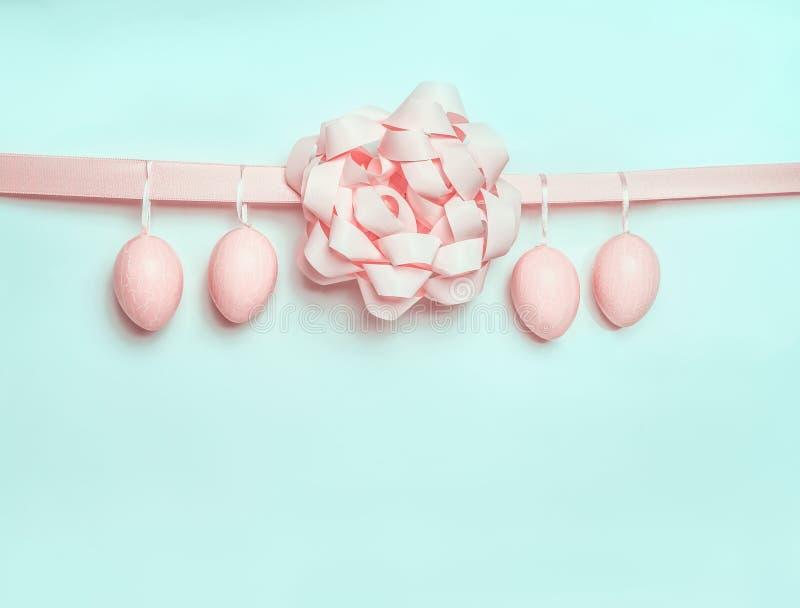 Pastelowych menchii Wielkanocni jajka wiesza na faborku z pięknym łękiem na bławym turkusowym tle Kreatywnie powitania pojęcie zdjęcie stock
