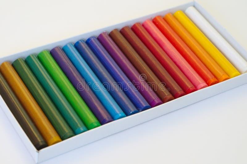Pastels colorés d'huile dans une boîte sur une feuille blanche photo libre de droits