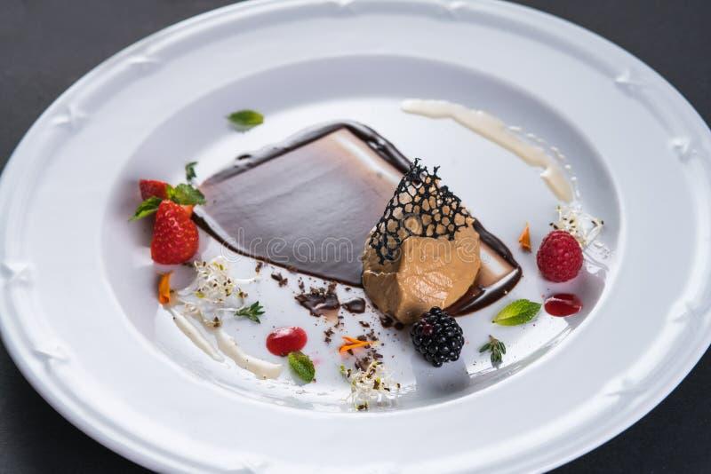 Pastetenfleisch wird mit Beeren und schwarzer Schokolade verziert Pastete von Fettleber Zartheit auf einer weißen Platte Restaura stockfotografie