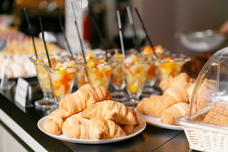 Pasticceria fresca, croissant croccanti di mattina, buffet della prima colazione dell'hotel Cocktail della frutta da tavola in ta immagini stock