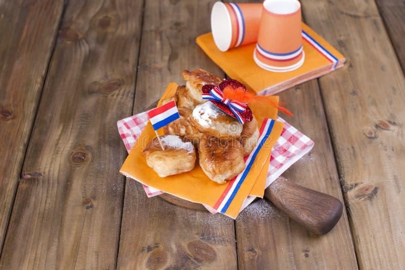 Pasticcerie dolci olandesi tradizionali Giorno di festa del re decorazione Cose arancio per la festa Bandierina dei Paesi Bassi immagini stock libere da diritti