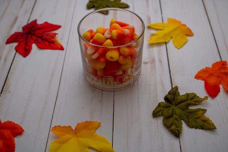 Pastillas de caramelo en Mini Glass rodeado por las hojas imágenes de archivo libres de regalías