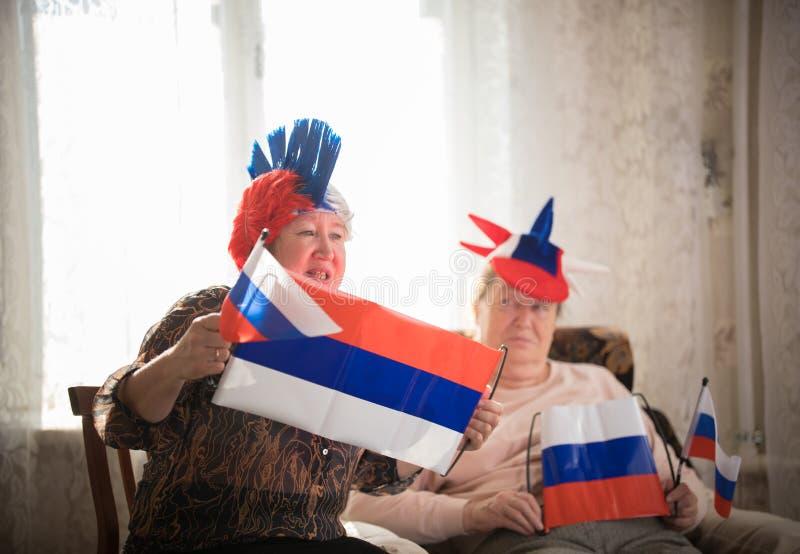 pastimes Steunt de bejaarden sportteam die met vlaggen tegen TV op backgrond van glanzend venster zitten stock foto's