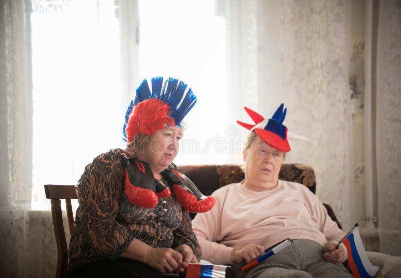 pastimes Steunt de bejaarden sportteam die met vlaggen tegen TV op backgrond van venster zitten stock foto's