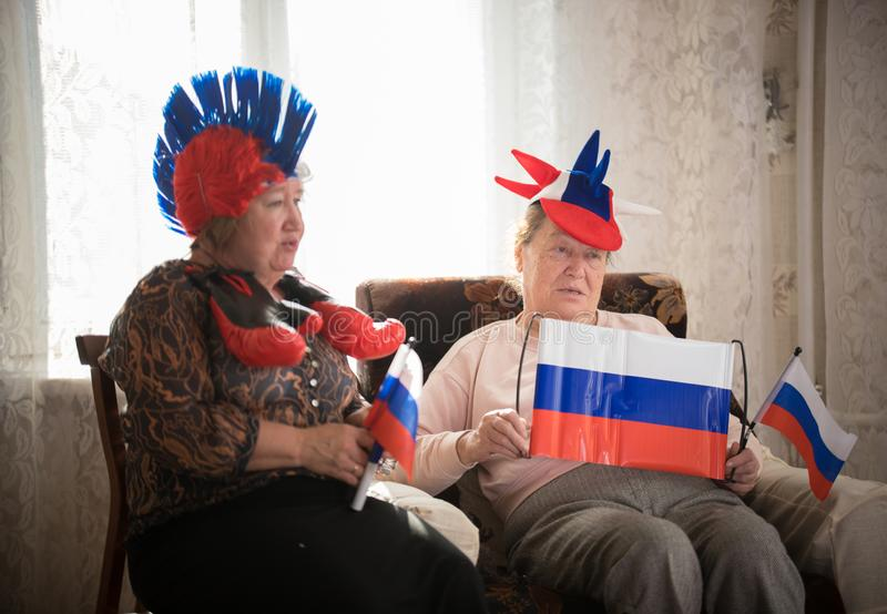 pastimes Steunt de bejaarden de zitting van het sportteam tegen TV op backgrond van glanzend venster royalty-vrije stock afbeeldingen