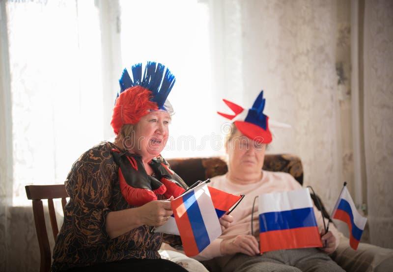 pastimes Steunt de bejaarden de zitting van het sportteam tegen TV op backgrond van venster royalty-vrije stock afbeelding