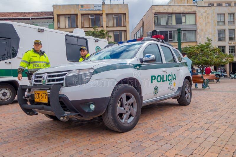 PASTO COLOMBIA - JULI 3, 2016: oidentifierade poliser som står bredvid en polisbil som parkeras på den centrala fyrkanten royaltyfri bild