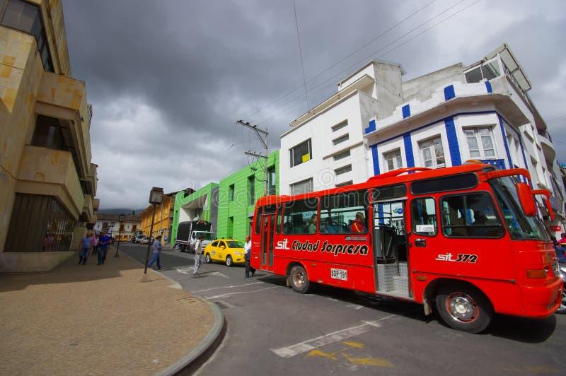 PASTO COLOMBIA - JULI 3, 2016: oidentifierat folk som korsar gatan, medan en offentlig buss väntar för att korsa royaltyfri fotografi