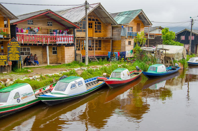 PASTO, COLOMBIA - JULY 3, 2016: some colorfull boats parked on the river next to some shops stock photo