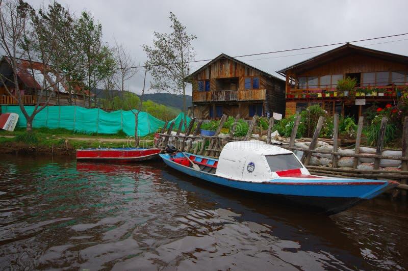 PASTO, COLOMBIE - 3 JUILLET 2016 : les petits bateaux se sont garés à côté d'un rivage avec quelques maisons en bois comme fond image stock