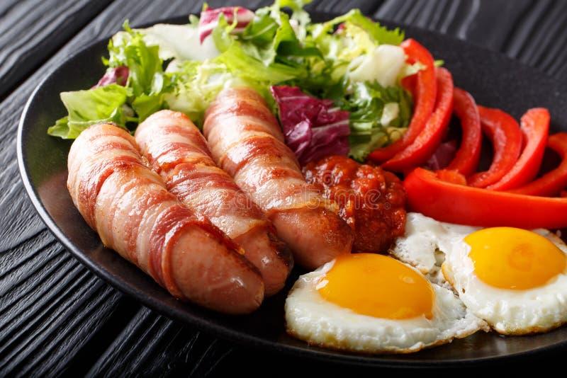 Pasto completo: Maiali in coperte - salsiccie fritte avvolte in bacon, e immagini stock