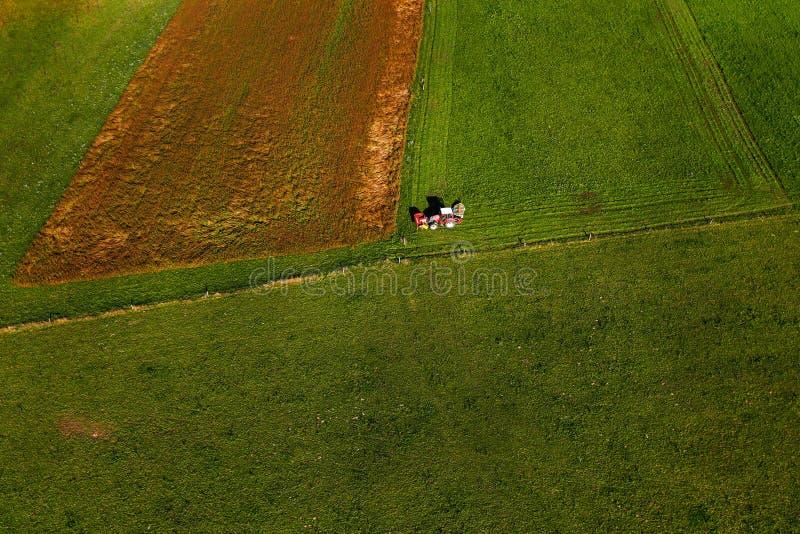 Pasto de siega del tractor en campo grande de la tierra cuidadosamente cultivada fotos de archivo