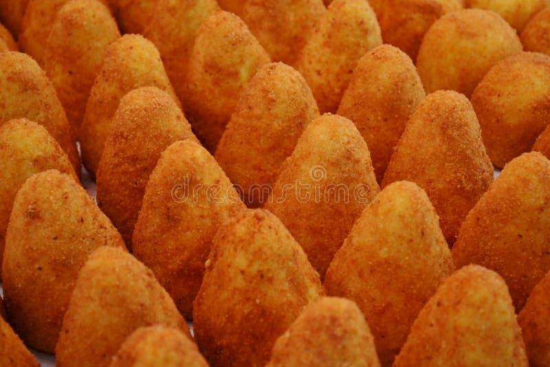 Pasto della cucina ed alimento italiani tradizionali della via dalla Sicilia - arancini - per la vendita nelle stalle di Natale d immagini stock