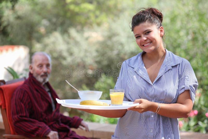 Pasto domestico del servizio di personale sanitario all'uomo anziano immagine stock libera da diritti