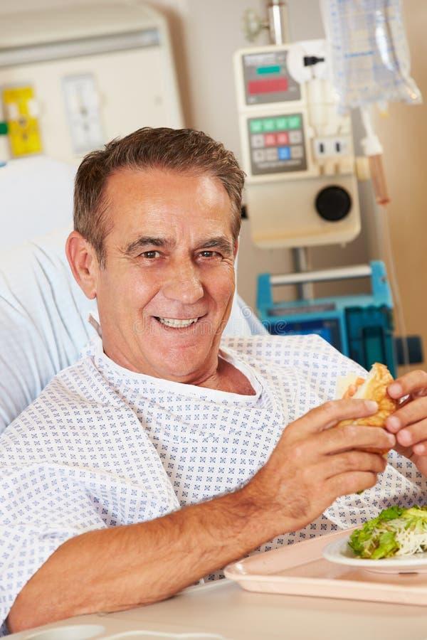 Pasto godente paziente maschio nel letto di ospedale fotografia stock libera da diritti