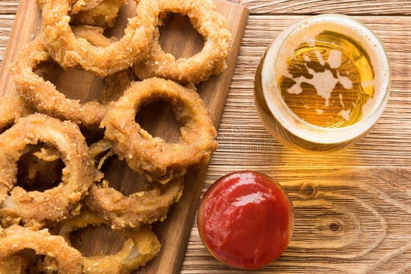 Pasto rapido tradizionale - anelli di cipolla con birra immagini stock libere da diritti