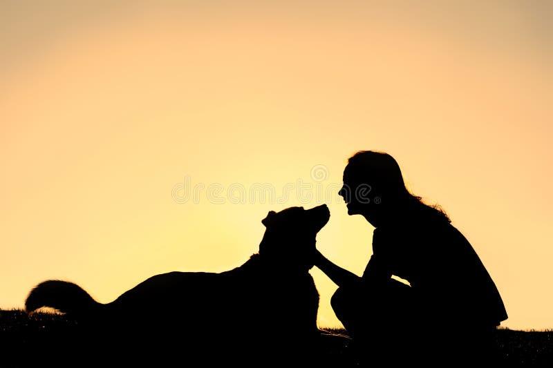 Pastor alemão Dog Silhouette das trocas de carícias felizes da mulher imagens de stock royalty free