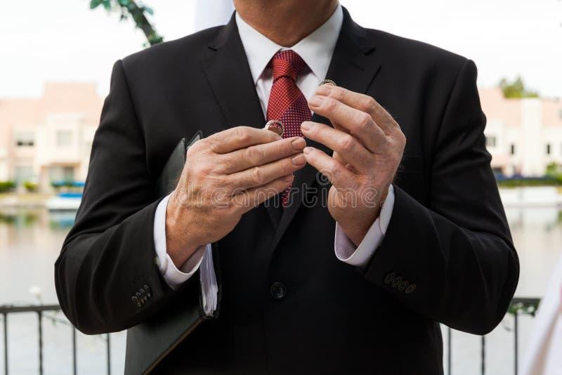 Pastor Holding Wedding Rings In le sue mani su cerimonia di nozze fotografia stock libera da diritti