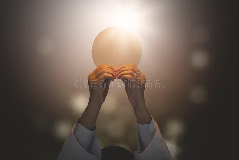 Pastor que levanta um pão brilhante do comunhão fotos de stock