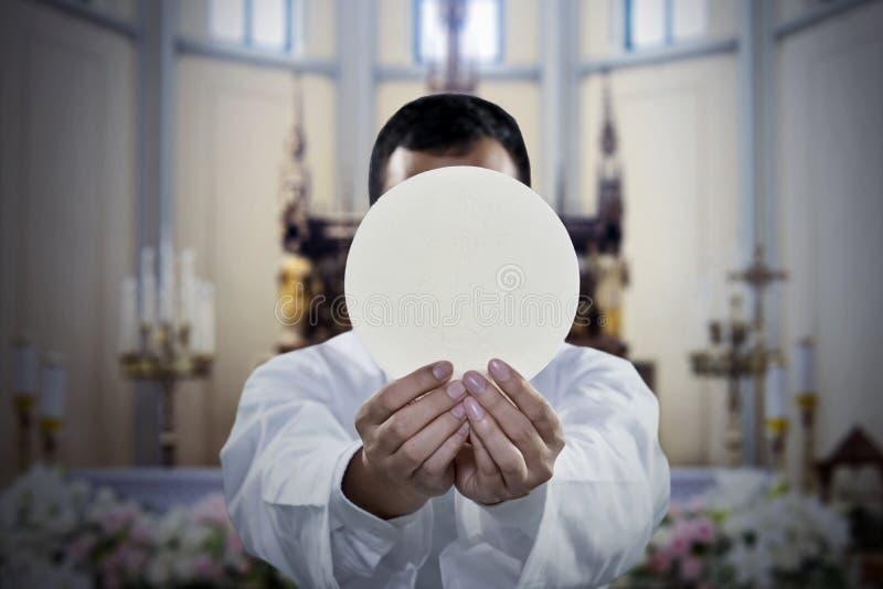 Pastor que sostiene un pan sacramental en iglesia imagen de archivo libre de regalías