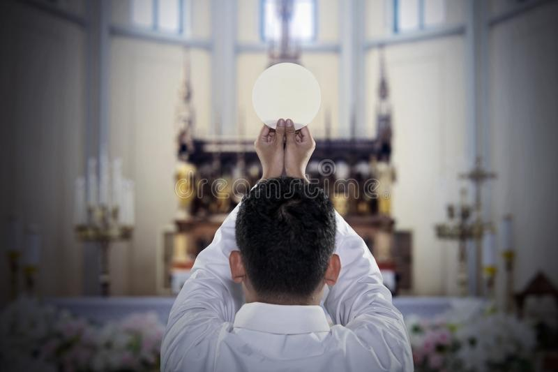 Pastor with sacramental bread in the church. Back view of pastor raising a sacramental bread during celebrating a mass in the church royalty free stock photography