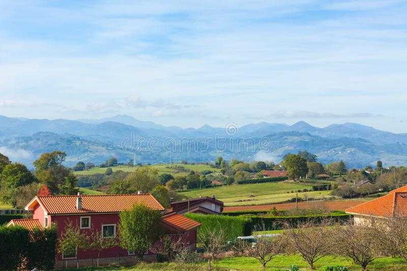 Pastoral landscape of Escamplero village with mountain peaks in the background. Asturias. Spain royalty free stock images