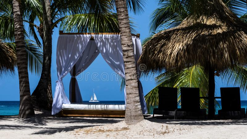Pastoral landscape of the ocean coast with palm trees and white canopies for relaxing in the hotel of the Dominican Repu. Pastoral landscape of the ocean coast stock images