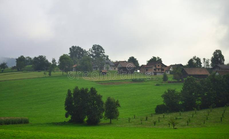 Pastoral scenery cloudy summer day view Slovenia Europe. Pastoral view of mountain houses in the Municipality of Grosuplje seen from A2 motorway on a misty july stock photography