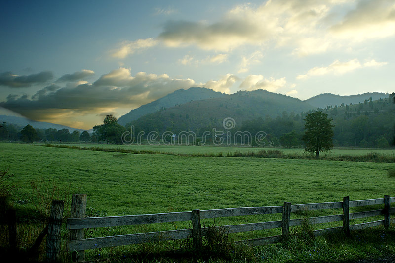 Pastoral Sunrise. The sun rises over a fenced field in West Virginia