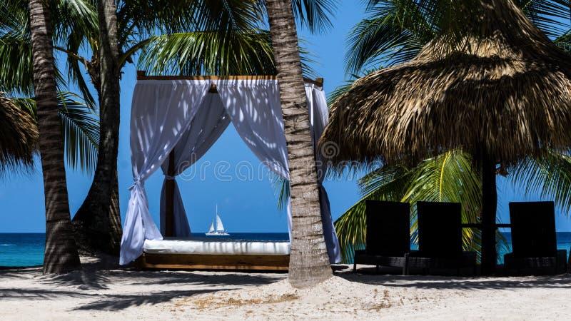 Pastoralny krajobraz oceanu wybrzeże z drzewkami palmowymi i białymi baldachimami dla relaksować w hotelu Dominikański Repu obrazy stock