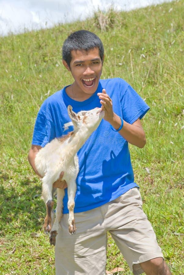 Pastore asiatico con la giovane capra immagini stock libere da diritti