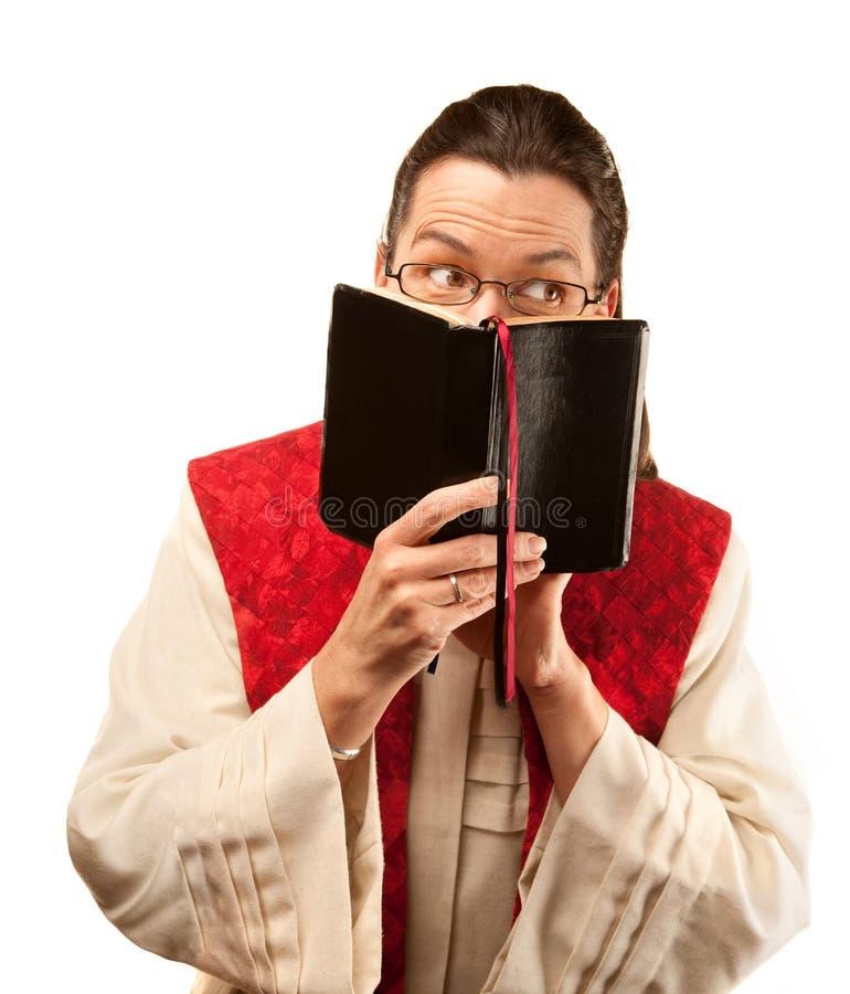 Pastore che osserva fuori da dietro la bibbia fotografia stock libera da diritti